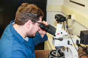 Penn State student Nathan Gendrue reviews the characterization of coal dust under a high-resolution microscope