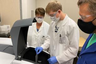 Connor Mosebey (center) loads a materials sample into a UV-Vis spectrometer