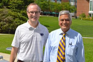 John Mauro, a glass expert and professor at Penn State, stands with his undergraduate adviser Arun Varshneya