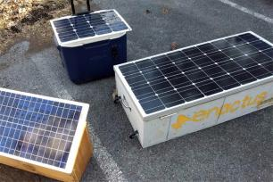 """A """"Solar Saver"""" box built by Penn State students, center, is displayed with other solar boxes bound for Puerto Rico."""