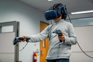 A woman uses virtual reality equipment at the Center for Immersive Experiences.