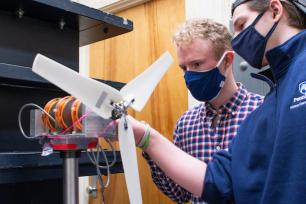 Josh Forrest (left),  and Eric Sarbacker, junior, assemble a test wind turbine to prepare for the upcoming wind competition