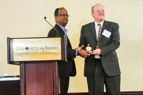 Shree Vikas, director of market intelligence and business analysis at ConocoPhillips, gives Andy Kleit the Senior Fellow Award