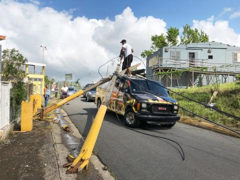 People attempt to remove broken power poles that landed on top a food truck in Puerto Rico after Hurricane Maria.