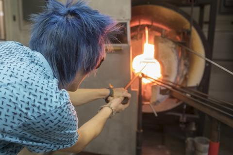 Briana Bennett heats glass in Penn State's fully-equipped glassblowing shop.