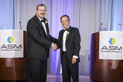 Zi-Kui Liu shakes hands with David Furrer at a ceremony in fall 2019