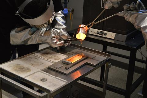 Conghang Qu, undergraduate student in materials science and engineering at Penn State, trims glass from a crucible