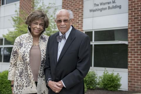 Warren and Mary Washington pose for photos at the entrance to the newly named Warren M. Washington Building