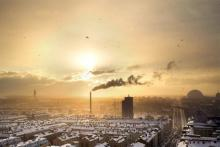 An industrial cityscape of a town filled with factories and air pollution at sunset.
