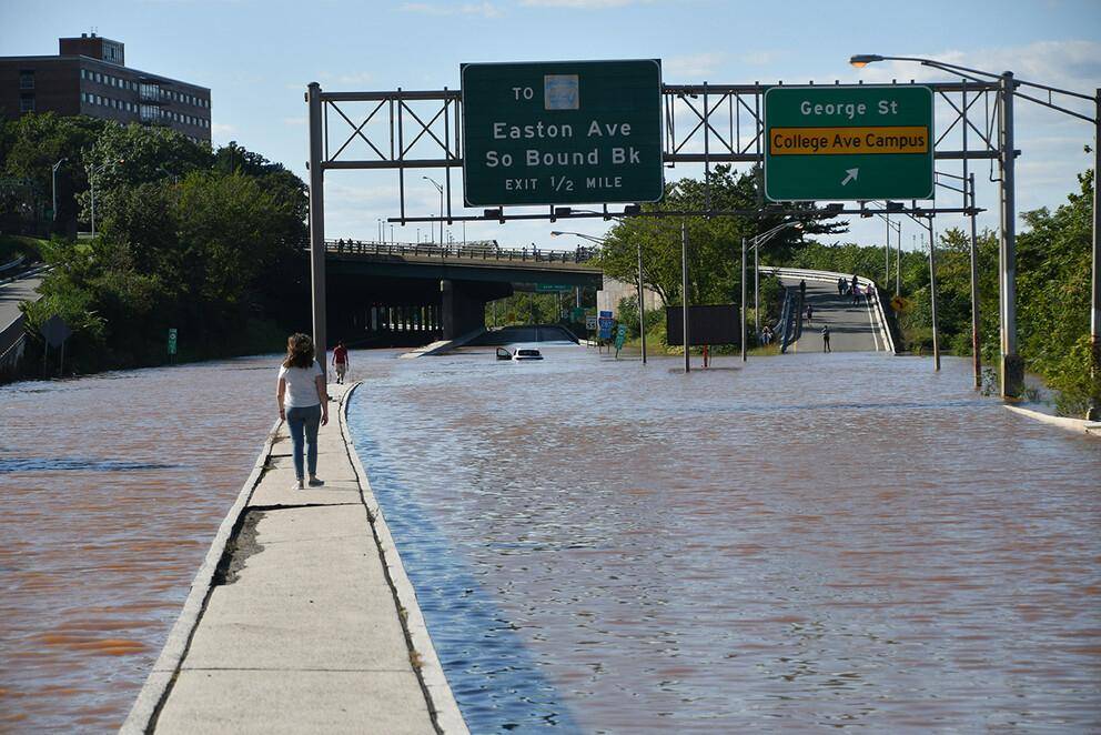 Here, a woman walks on median in the middle of a flooded highway in New Brunswick, New Jersey, after Hurricane Ida