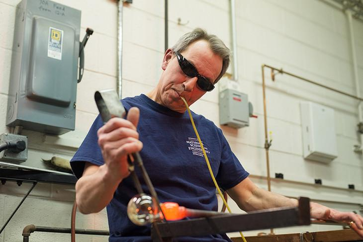 Distinguished Professor of Materials Science and Engineering Carlo Pantano shapes glass at his glass blowing studio in the Hosler Building. Pantano, who has dedicated almost 40 years to studying the surface of glass, retires June 30.