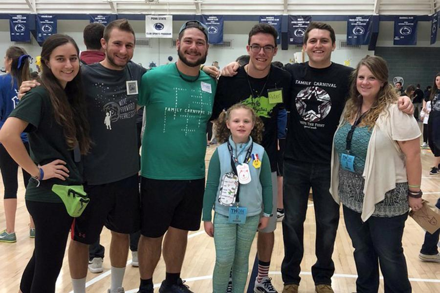 Friends and EMS THON members pose with one of the Four Diamonds families at the THON Family Carnival held at the IM Building.