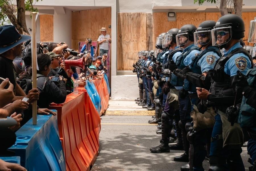 """An image from the film """"DisemPOWERed: Puerto Rico's Perfect Storm"""" shows protesters stand facing police officers in Puerto Rico."""