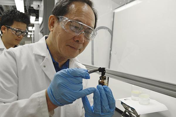 Michael Chung, professor of materials science at Penn State, holds a solid chunk of oil that is able to be reused.