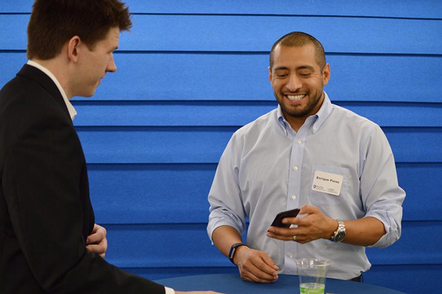 Alumnus Enrique Perez chats with a student