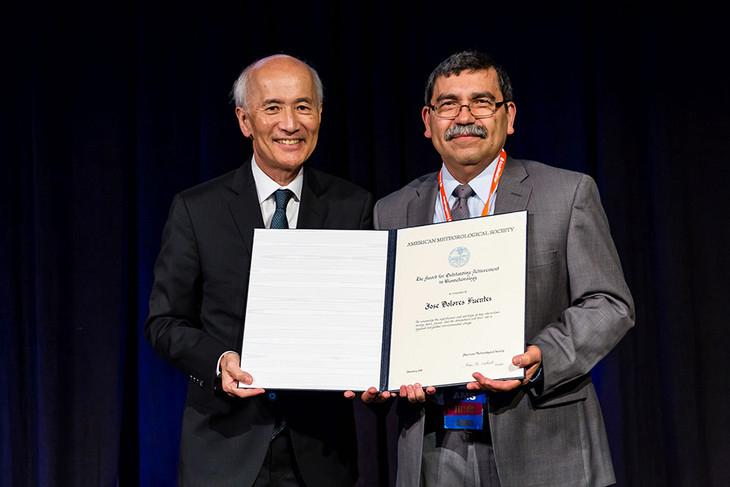 Jose Fuentes, right, accepts an award from the American Meteorological Society