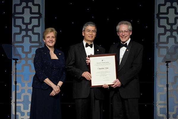 George A Olah Award recipient Chunshan Song (center) is presented his award by John Adams (right) and  Bonnie A. Charpentier