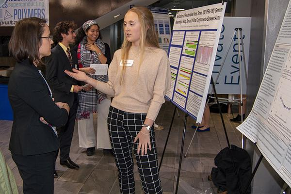 Allison Beese, left, discusses research with student Anna Wickenheisser during the WISER/MURE/FURP symposium
